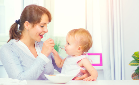 Mother feeding her baby girl with a spoon. Baby food. Healthy family 写真素材