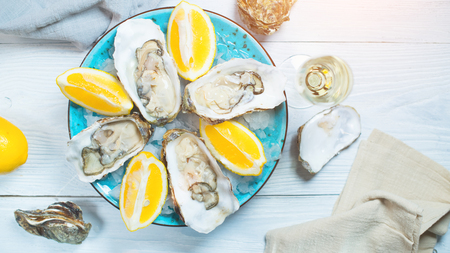 Fresh oysters close-up on blue plate, served table with oysters, lemon and champagne in restaurant. Gourmet food. Tabletop view Stockfoto