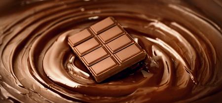 Chocolate bar over melted dark chocolate swirl liquid background. Confectionery concept backdrop. Sweet dessert Foto de archivo