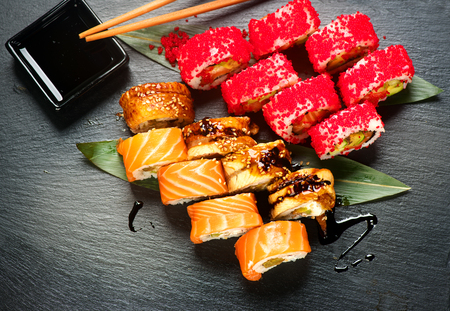 Sushi with chopsticks and soy sauce. Sushi roll japanese food in restaurant. California Sushi roll set with salmon, vegetables, flying fish roe and caviar closeup. Japan restaurant menu Stock Photo