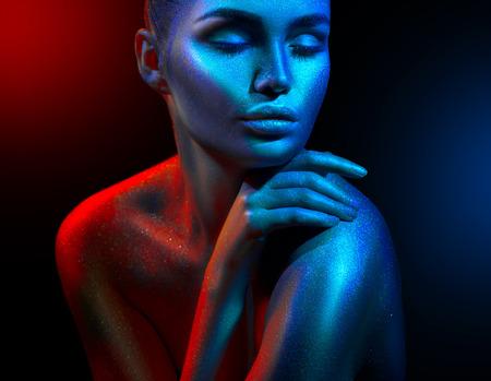 Mannequin femme dans des étincelles lumineuses colorées et des néons qui posent en studio, portrait de belle fille. Maquillage vif coloré de conception d'art