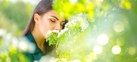Beauty young woman enjoying nature in spring apple orchard, Happy beautiful girl in a garden with blooming fruit trees Stok Fotoğraf