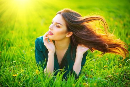 Beauty woman lying on the field enjoying nature. Beautiful brunette girl with healthy long flying hair. Summer green grass