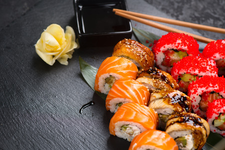 Sushi rolls closeup. Japanese food in restaurant. Roll with salmon, eel, vegetables and flying fish caviar on black slate background