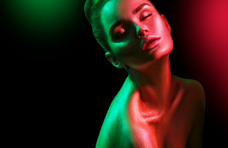 Fashion model woman in colorful bright sparkles and neon lights posing in studio, portrait of beautiful sexy girl. Art design colorful vivid makeup Stock Photo