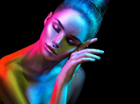 Mujer modelo de moda en coloridos destellos brillantes y luces de neón posando en el estudio, retrato de una chica hermosa. Diseño de arte colorido maquillaje vivo.