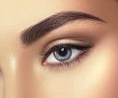 Primo piano dell'occhio azzurro della giovane donna. Occhio a macroistruzione che osserva in su, isolato su priorità bassa bianca
