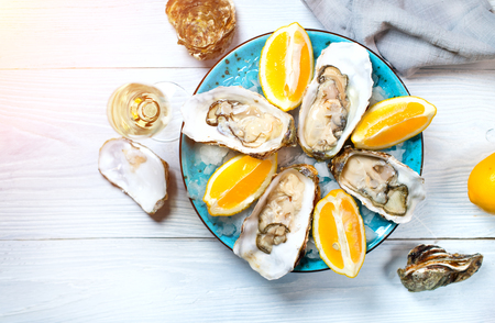 Fresh oysters close-up on blue plate, served table with oysters, lemon and champagne in restaurant. Gourmet food. Tabletop view 스톡 콘텐츠