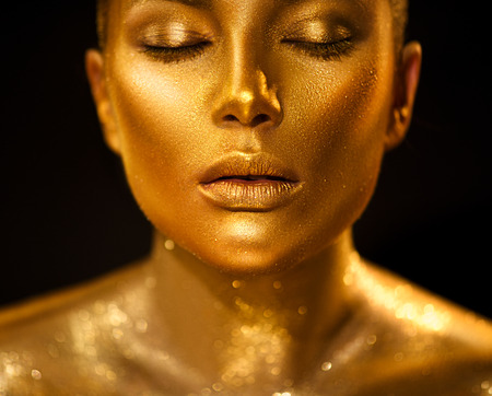 Golden skin woman face. Fashion art portrait closeup. Model girl with holiday golden glamour shiny professional makeup. Gold jewelry, accessories Stockfoto