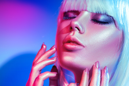 Fashion model woman in colorful bright sparkles and neon lights posing in studio, portrait of beautiful girl, trendy glowing make-up