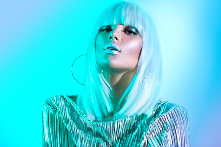 High fashion model girl in colorful bright neon lights posing in studio. Portrait of beautiful sexy woman in white wig and silver trendy glowing makeup 免版税图像