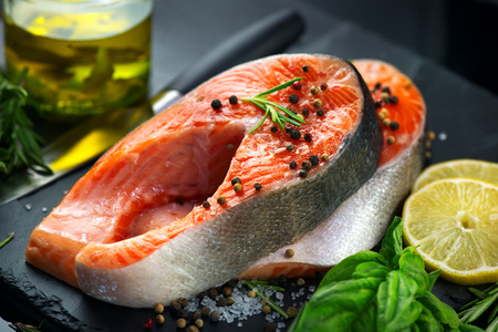 Salmon. Raw trout fish steak with herbs and lemon on black slate background. Cooking, seafood. Healthy eating concept