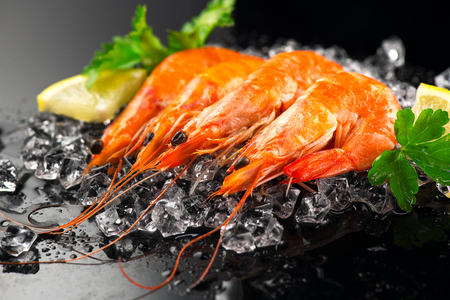 Shrimps. Fresh prawns on a black background. Seafood on crashed ice with herbs. Healthy food, cooking Stock Photo