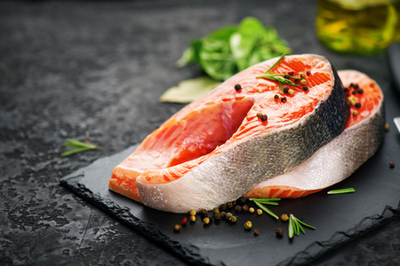 Salmon. Raw trout fish steak with herbs on black slate background. Cooking, seafood. Healthy eating concept