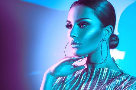 Fashion model brunette woman in colorful bright neon lights posing in studio. Beautiful girl, trendy glowing makeup, metallic silver lips