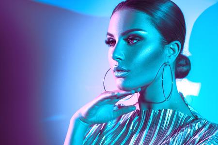 Modello di moda donna castana in luci al neon luminose colorate in posa in studio. Bella ragazza, trucco luminoso alla moda, labbra argento metalliche