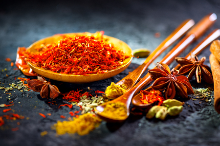 Saffron. Various Indian Spices on black stone table. Spice and herbs on slate background. Cooking ingredients 스톡 콘텐츠