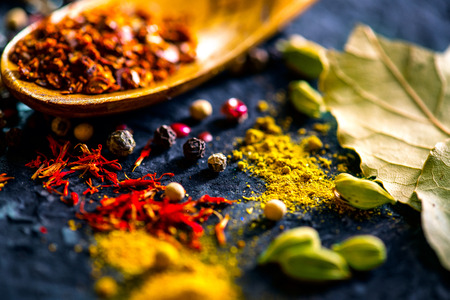 Spices. Various Indian spices on black stone table. Spice and herbs on slate background. Cooking ingredients