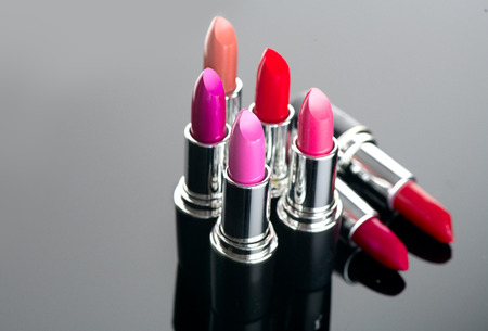 Lipstick. Professional makeup and beauty. Lipstick tints palette closeup. Colorful lipsticks over black background