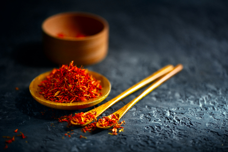 Saffron spices. Saffron on black stone table in a wood bowl and a spoon. Spice and herbs on slate background. Cooking ingredients Standard-Bild - 105404286