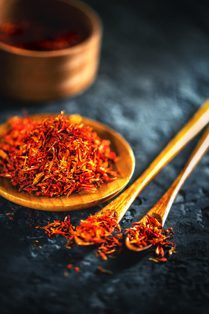 Saffron spices. Saffron on black stone table in a wood bowl and a spoon. Spice and herbs on slate background. Cooking ingredients Standard-Bild - 105270897