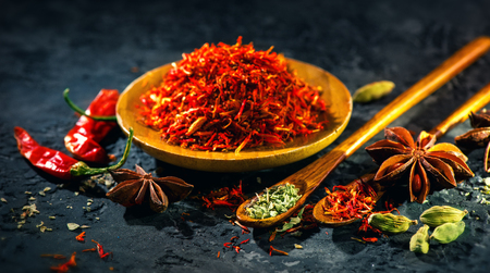 Saffron. Various Indian Spices on black stone table. Spice and herbs on slate background. Cooking ingredients Stock Photo