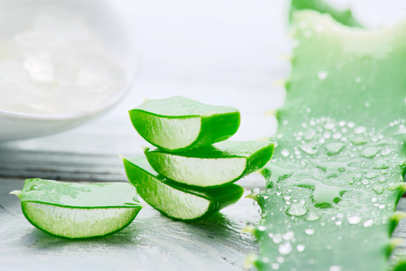 Aloe Vera gel closeup on white wooden background. Organic sliced aloevera leaf and gel, natural organic cosmetic ingredients for sensitive skin, alternative medicine. Skincare concept Stock Photo - 105511645