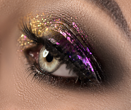 Beautiful eye makeup with colorful sparks. Beauty bright fashion holiday smoky eyes makeup. Purple and golden glitter eyeshadows 写真素材