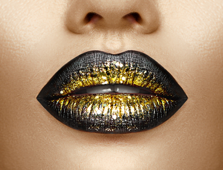 Lips makeup. Beauty high fashion gradient lips makeup sample, black with golden color. Sexy mouth closeup. Lipstick Standard-Bild