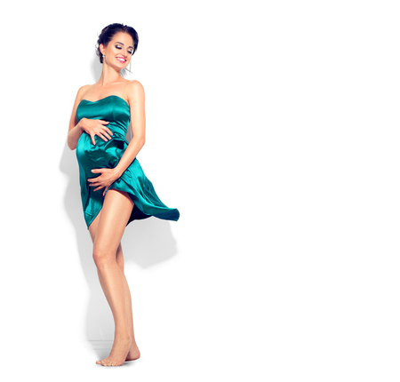 Beauty pregnant woman in fashion fluttering green silk dress posing in studio. Full length portrait isolated on white background. Pregnancy