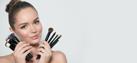 Ragazza di modello di bellezza, artista di trucco che tiene insieme di pennelli per il trucco e sorridente. Bella giovane donna castana con pelle e trucco perfetti. Pelle perfetta