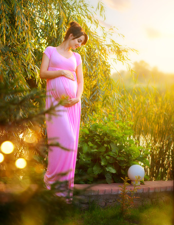 Pregnant happy woman caressing her belly in summer park. Full length pregnant beauty woman outdoor portrait. Healthy pregnancy concept