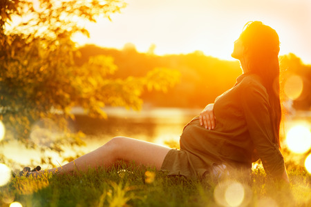 Pregnant woman sitting on green grass in summer park, enjoying nature. Healthy pregnancy concept Stok Fotoğraf