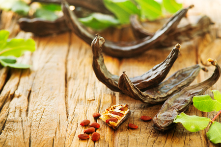 Carob. Healthy organic sweet carob pods with seeds and leaves on a wooden table. Healthy eating, food background