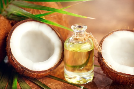 Coconut oil in a bottle with coconuts and green palm tree leaf. Healthy eating. Skincare concept Stock Photo