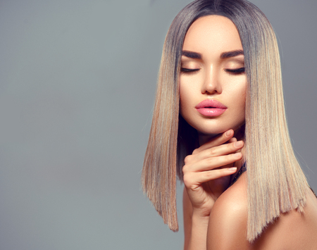 Fashion hairstyle. Ombre dyed hair. Beauty Model girl with perfect healthy hair and beautiful makeup posing in studio, young woman portrait on grey background Foto de archivo
