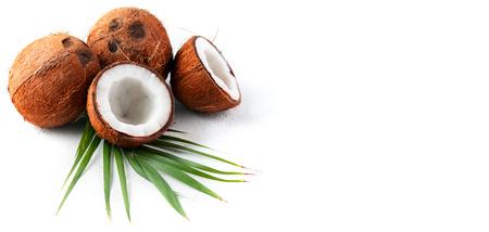 Coco con cocos hoja de palmera aislada sobre fondo blanco. Nuez de coco fresca. Comida sana, concepto de cuidado de la piel. Comida vegana Foto de archivo
