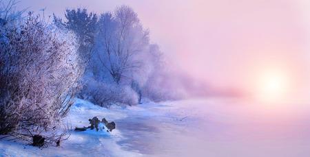 Mooie winterlandschap scène achtergrond met sneeuw bedekte bomen en ijskoude rivier. Schoonheid zonnige winter achtergrond. Wonderland. IJzige bomen in sneeuwbos Stockfoto
