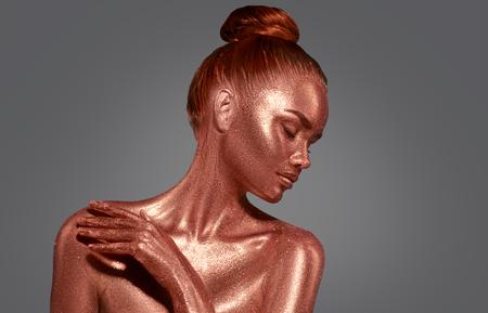 Golden skin beauty woman portrait. Fashion model girl with holiday golden makeup. Body art 版權商用圖片