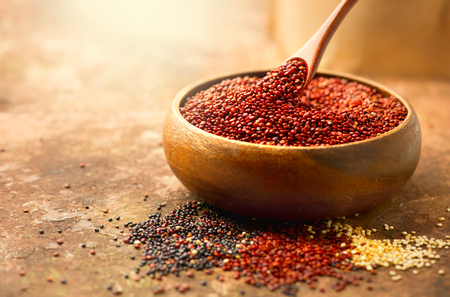 Quinoa. Red, black and white quinoa grains in a wooden bowl. Healthy food. Chenopodium quinoa Banco de Imagens