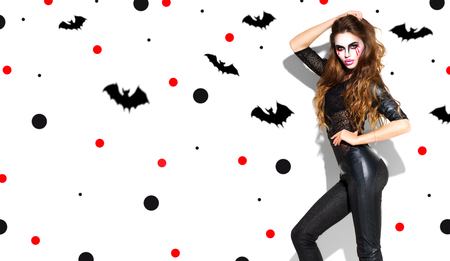Halloween. Holiday party girl makeup. Beautiful young woman with bright vampire make-up and long hair posing in witches costume
