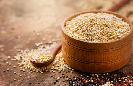 Quinoa. White quinoa grains in a wooden bowl. Healthy food. Dieting concept. Seeds of white, red and black quinoa - Chenopodium quinoa