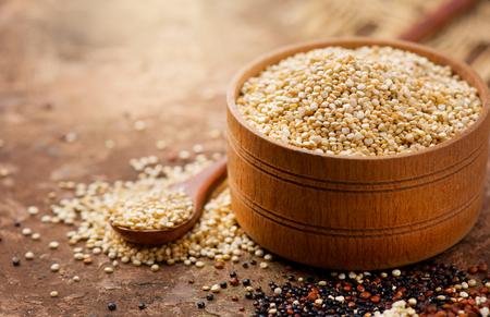 Komosa ryżowa. Białe ziarna komosy ryżowej w drewnianej misce. Zdrowe jedzenie. Pojęcie diety. Nasiona komosy ryżowej białej, czerwonej i czarnej - Chenopodium quinoa