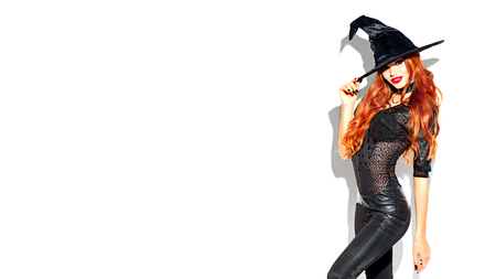 Halloween. Sexy witch with bright makeup and long red hair. Beautiful young woman posing in witches sexy costume over white background 版權商用圖片