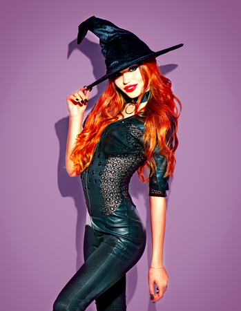 Halloween. Sexy witch with bright makeup and long red hair. Beautiful young woman posing in witches sexy costume over violet background Stock Photo
