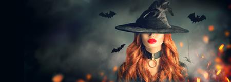 Schöne junge Frau im Hexenhut mit dem langen gelockten roten Haar über gruseligem dunklem magischem Waldhintergrund