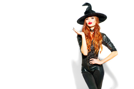 Halloween. Sexy witch with bright holiday makeup. Beautiful young woman posing in witches costume over white background 版權商用圖片