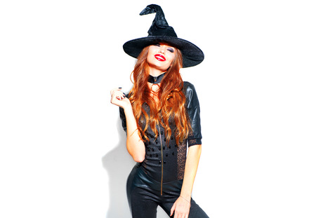 Halloween. Sexy witch with bright holiday makeup. Beautiful young woman posing in witches costume over white background Banco de Imagens