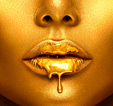 Gold paint drips from the lips, golden liquid drops on beautiful model girl's mouth, creative abstract makeup. Beauty woman face