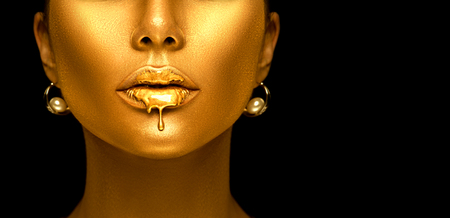 Gold paint drips from the lips, golden liquid drops on beautiful model girl's mouth, creative abstract makeup.